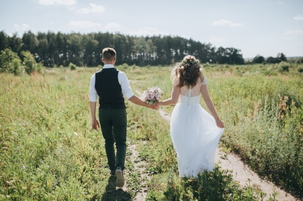guy in a vest and a girl in a white wedding dress with a bouquet in the hands go on the field